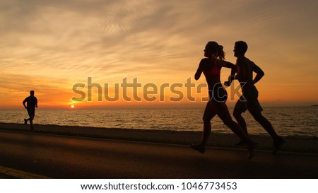 SILHOUETTE: Orange sun rays illuminate athletic man and woman meeting another jogger on relaxing evening jog. Unrecognizable young couple runs along ocean road in front of picturesque summer sunset. #1046773453
