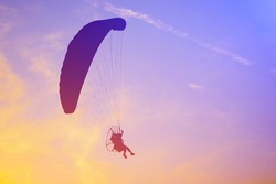 silhouette paramotor with sunlight effect on the sky in the evening:Close up,select focus with shallow depth of field:ideal use for background