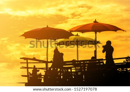 silhouette parasols on wooden  balcony terrace on the hill with photographer taking photos in sunset #1527197078