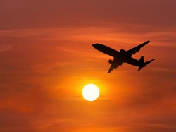 Silhouette passenger airplane flying in to sky during sunset