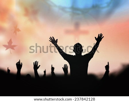 Silhouette people raising hands over blurred crown of thorns and the cross on nature background