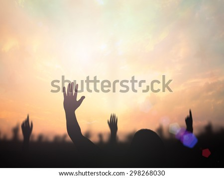 Silhouette people raising hands over blurred the cross on beautiful golden autumn sunset background.