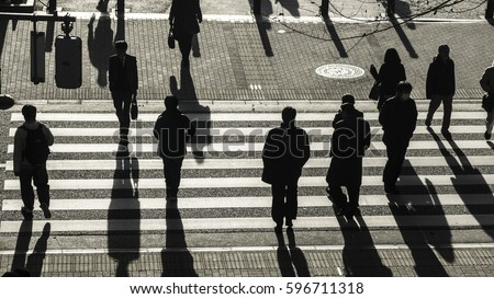 silhouette people walk on pedestrian crosswalk at the junction street of business city at the evening sunset with the dark shadow of people on the road (top aerial view) #596711318