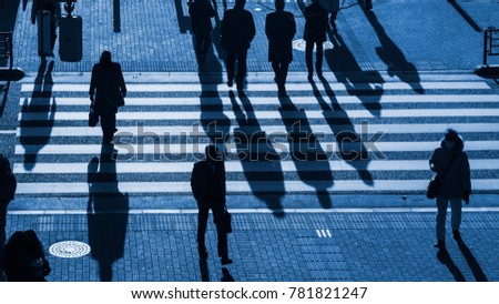 silhouette people walk on pedestrian crosswalk at the junction street of business city at the evening sunset with the dark shadow of people on the road (top aerial view)