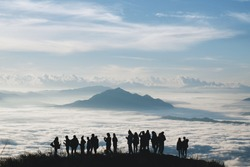 Silhouette peoples on top the mountain view point and sea of mist, Thailand.