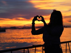 Silhouette photo of an Asian woman standing alone,holding hands in heart shape and watching ocean during sunset in Pattaya, Thailand