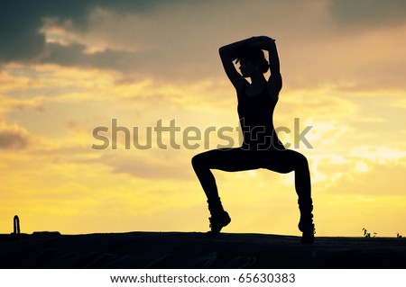 Silhouette photo of dancing woman in modern pilates style over sunset landscape. Yoga