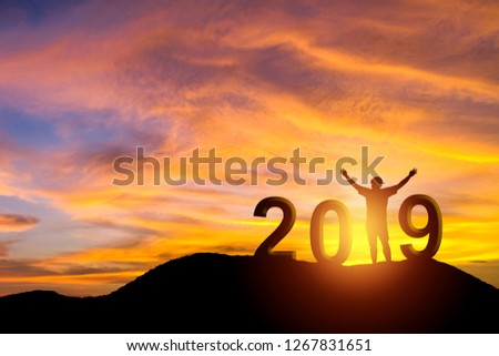 Silhouette photo of the man standing on mountain for Happy new year 2019. Celebration new year, happy victory and success concept.