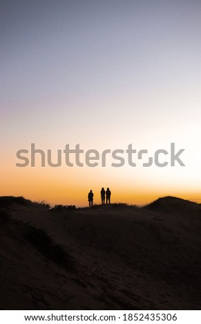 Silhouette photo of three people standing on top of a mountain at sand dunes north of Sydney Foto stock ©