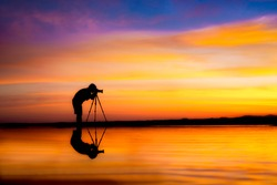 Silhouette Photographer take photo dramatic colorful sunset sky on beach in twilight.