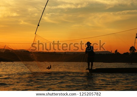 Silhouette picture of fisherman using the square dip net for fishing in twilight timing. #125205782