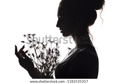 silhouette portrait of a beautiful girl with a bouquet of dry dandelion flowers, face profile of a dreamy young woman on a white isolated background, the concept of beauty and nature