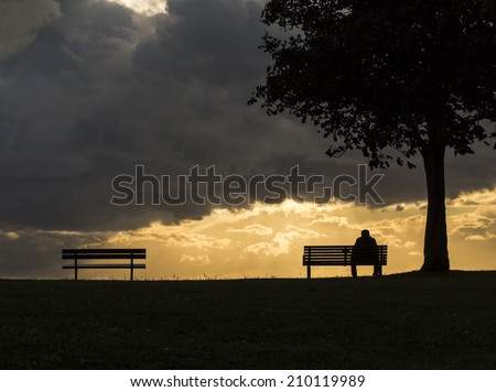 Silhouette portrait of a lonely anonymous man sitting on a bench as dark clouds above him roll, with the sun beginning to set behind