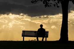Silhouette portrait of a lonely anonymous man sitting on a bench watching the dark skies above roll by.