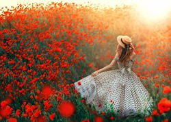 Silhouette romantic happy fantasy woman, back rear view. Girl walks enjoy blooming hill red poppies meadow. Vintage fashion 50s retro white dress, black polka dots, straw hat. Bright Sunset sun light