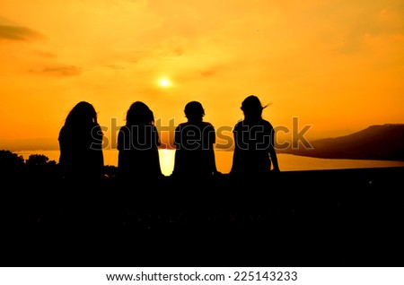 silhouette scene of girl gang relax and watching sunset