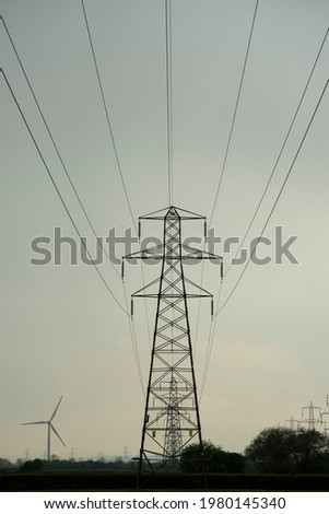 Silhouette shadow of transmission tower, or power line. These are scattered throughout the UK, so that people can make landline phone calls to others, via a wired connection. Copy space to add text. Stok fotoğraf ©