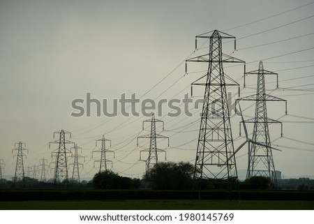 Silhouette shadow of transmission towers, or power lines. These are scattered throughout the UK, so that people can make landline phone calls to others via a wired connection. Copy space to add text. Stok fotoğraf ©