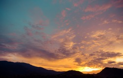 silhouette shot image of mountain and sunset sky in background.(vintage tone)