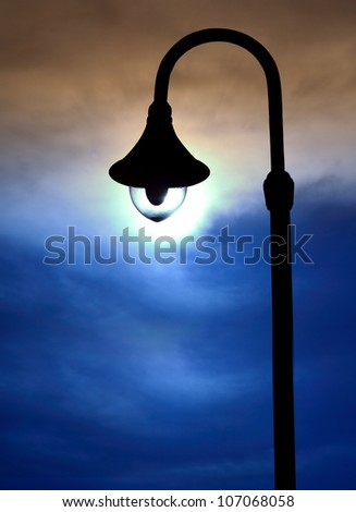 silhouette street lamps on evening sky
