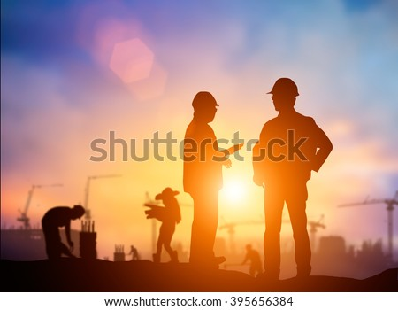Silhouette Successful male engineer standing survey work on construction over blurred Worker in  construction site over blurred nature. examination, inspection, survey