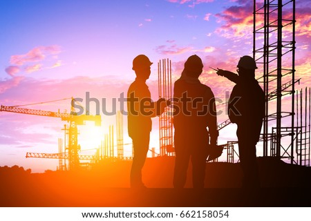 Silhouette Teams engineer looking construction worker in a building site at sunset #662158054