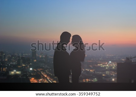 silhouette teen couple lovers in romance moment on blurred dark night city downtown background:teenager in love concept:valentines:love story movie conception.happy people dating conceptual.