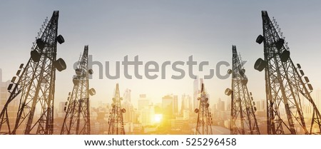 Silhouette, telecommunication towers with TV antennas and satellite dish in sunset, with double exposure city in sunrise background - Shutterstock ID 525296458
