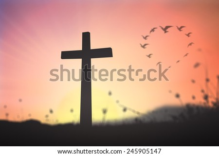 Silhouette the cross over blurred birds flying in the shape of heart against a evening or morning sky in the background.