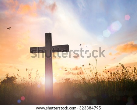 Silhouette the cross over over blurred beautiful autumn sunset with amazing light background.