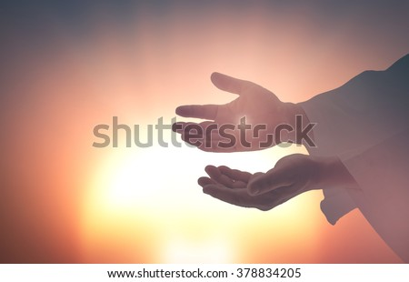 Silhouette the hands of Jesus Christ opening palm up and showing scars on blurred spiritual light background. Resurrection Humble Redeemer Eucharist Blessed Christian Give Trust Nail Religion concept.