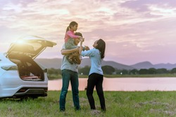 Silhouette the happy family of three people, mother, father and child in front of a sunset sky; asian family are happy sitting in the open trunk of a car; travel nature trip.