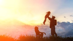 Silhouette the happy family of three people, mother, father and child in front of a sunset sky.