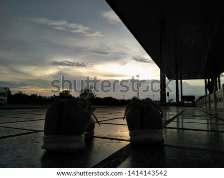 Silhouette, The shadow of sneaker and evening sky in the evening #1414143542
