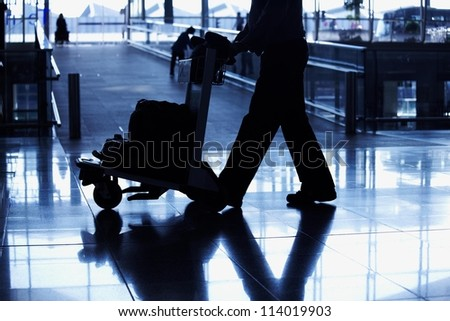 silhouette travelling peoples lifestyle in airport in black and white with blue tones
