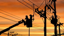 Silhouette two electricians with disconnect stick tool on crane truck are working to install electrical transmission on power pole with blurred sunrise sky background in technology concept