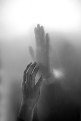 silhouette two lover touching hand separate by glasses in black and white