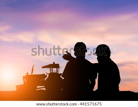 silhouette two men to operate heavy machinery plowed soil in preparation for planting crops. The main industry of the world. concept food crop. concept to save the world.