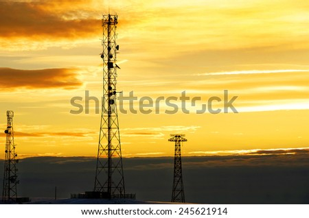 Silhouette view of cellphone antenna under twilight sky.