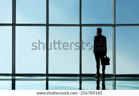 Silhouette view of young businessman is standing in modern office with panoramic windows.