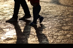 Silhouette walking step of father and son with light and shadow on the ground