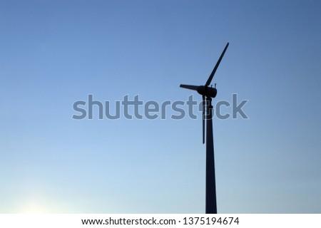 silhouette wind turbine generating electricity pole over clear blue sky #1375194674