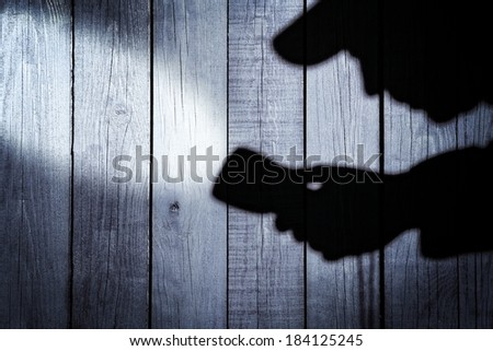 Silhouette with a Searchlight on Grungy Wooden Background.  #184125245