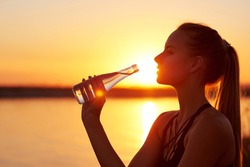 Silhouette woman drinking water from bottle after run or yogaon the beach. Fitness female profile at sunset, concept of sport and relaxation