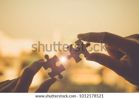 Silhouette Woman hands connecting couple puzzle piece against sunrise effect, businesswoman holding jigsaw with sunset background. Business solutions, target, success, goals and strategy concepts