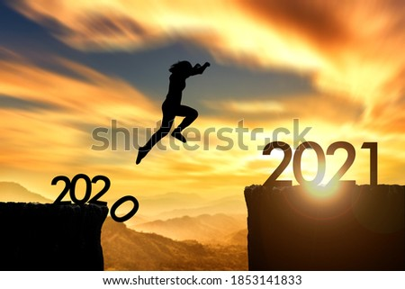 Silhouette woman jumping from 2020 cliff to 2021 cliff on sunrise time