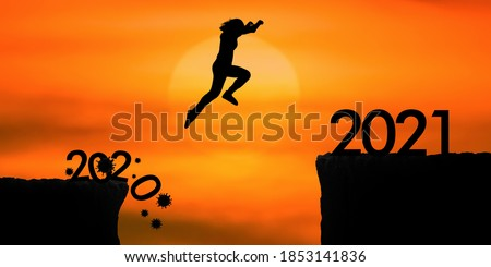 Silhouette woman jumping from 2020 cliff to 2021 cliff on sunrise time Сток-фото ©
