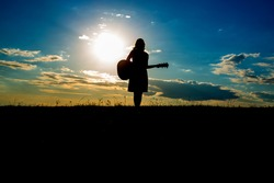 Silhouette woman playing guitar in the sunset