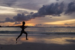 silhouette woman running on the beach with a beautiful sunset in background