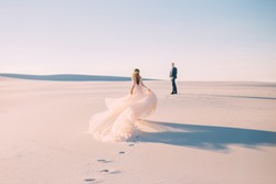 silhouette woman runs meet man. Dress  very long train fabric flies wind. tourist Art Photo back without face turned away rear view. UAE Dubai Desert white sand sunset concept happy Valentine's Day